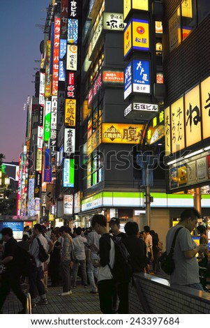 SHINJUKU, TOKYO - MAY 31, 2014: Crowd of people in Shinjuku, downtown Tokyo. About 800,000 people live and work here. The biggest commercial and night life town in Japan, called as sleepless city.