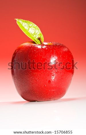 Shinny red apple on red gradient background with green leaf and water droplets