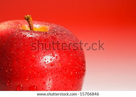 Shinny red apple on red gradient background with water drops