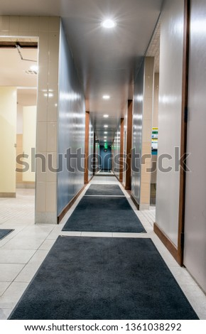 Shiny and clean hallway in mens locker room illuminated with bright LED lights along carpeted floors.