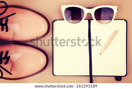 Shiny beige shoes on low heels, white sunglasses, wooden pencil and small black paper notebook. Vintage style edition.