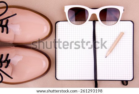 Shiny beige shoes on low heels, white sunglasses, wooden pencil and small black paper notebook. Beige background