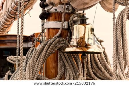 Shiny brass ship\'s bell on a vintage sailboat.