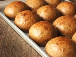 Shiny brown coffee flavored bread buns in baking tray on wooden table