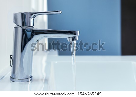 Shiny chrome faucet. Water flows into the sink. Photo stock ©