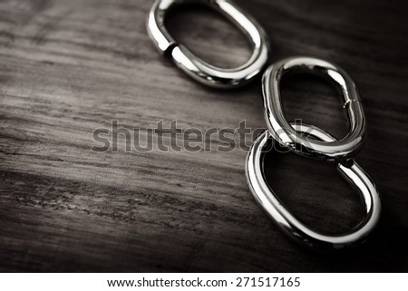 Shiny Chrome or silver chain links on a grungy wooden table. shallow depth of field.