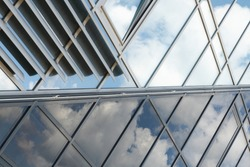shiny glass wall with darkening glass and sheer glass joint with sky reflection, mirrorlike