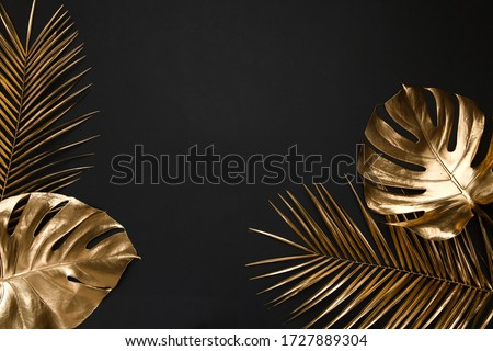 Shiny glossy golden painted tropical date palm and monstera leaves creatively arranged on black paper background. Empty space for copy, room for text. Trendy luxury border frame flatlay design.