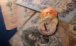 Shiny gold, silver and copper bitcoin coins lying on a dark black flat slate stone with old Russian tsarist notes from the 19th and early 20th centuries.