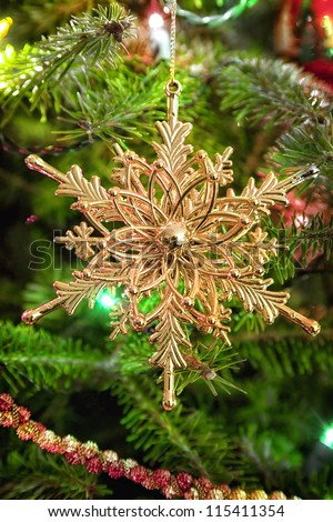 Shiny golden filigree snowflake ornament hanging in the Christmas tree.