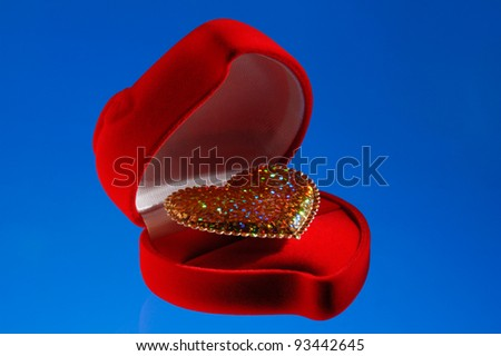 Shiny golden heart in a red jewelry box isolated on blue background