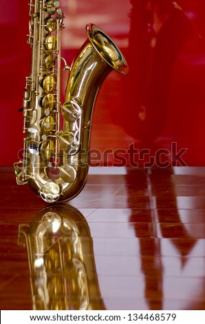 Shiny golden shimmering saxophone on polished wooden floor, isolated with red background and optical reflection.