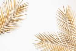 Shiny golden tropical palm leaves closeup border frame isolated on white background. Chic wedding invitation card template. Empty space, room for text.