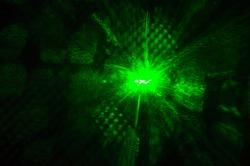 Shiny green laser light glowing in the dark in the night club.