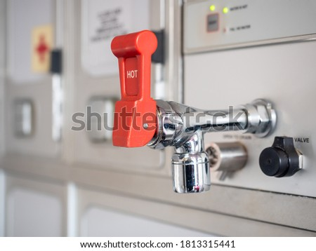 shiny hot water tap with red lever in aircraft galley. Stockfoto ©