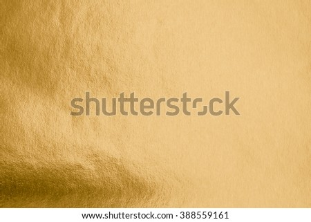 Shiny hot yellow gold foil leaf paper decorative texture background: Crumpled bright brilliant festive glossy metallic look textured backdrop: Aluminium tin metal steel material for design decoration