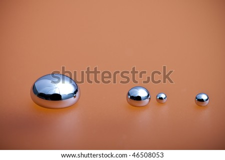 Shiny Mercury drops on a orange background