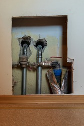 Shiny metal and copper water pipes in the wall with a water meter. Plastic tube with wadding and water valve. Holes in the concrete wall and plasterboard wall during repairs inside.
