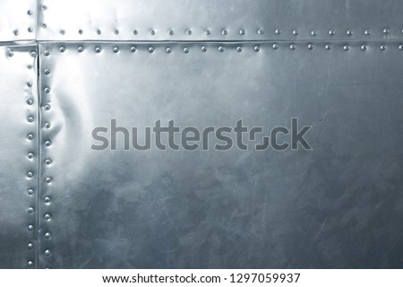 Shiny metal plate with rivets, riveted aluminum sheet with horizontal and vertical rows of rivets along seams, a military background
