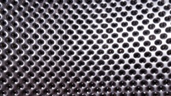 Shiny metal surface with lots of round holes. Perforated stainless metal. Fragment of a washing machine drum.