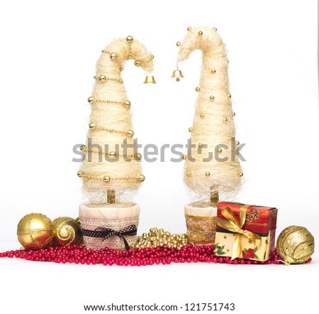 Shiny miniature Christmas trees made of sisal with beads and present - stock photo