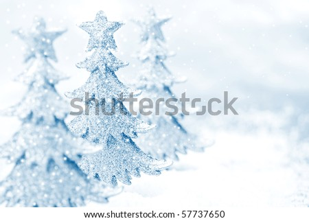 Shiny miniature tree ornaments on silver background with snow. High key blue toned macro with extremely shallow dof.  Copy space included.