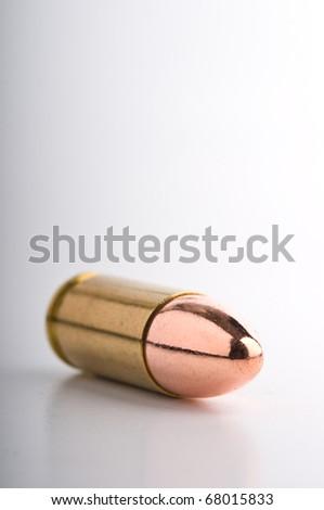 Shiny mm pistol cartridge on its shadow