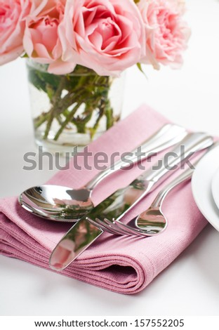Shiny new cutlery, silverware and a napkin with flowers, close-up on white background