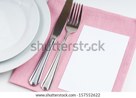 Shiny new cutlery, silverware and cardboard card close up on white background