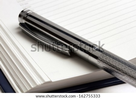 shiny pen lying on the diary