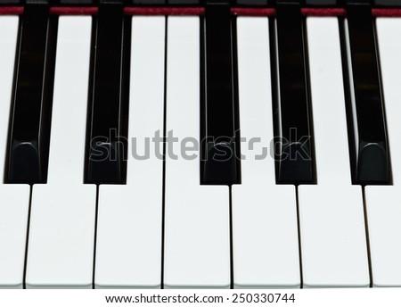 Shiny piano keys on grand piano.