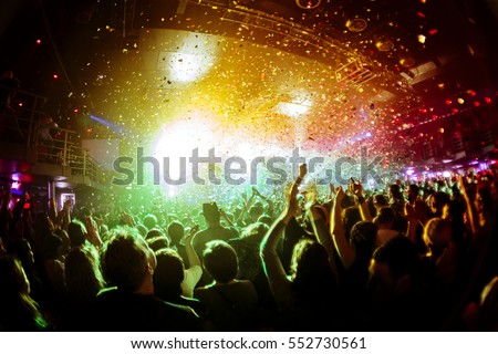 Photo of  shiny rainbow confetti during the concert and the crowd of people silhouettes with their hands up