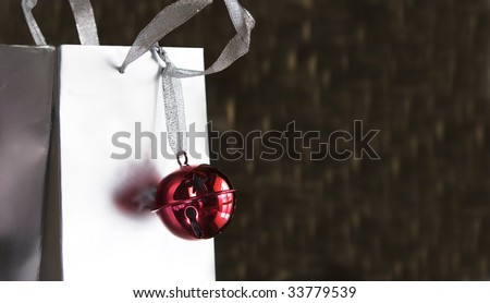 shiny red jingle bell on silver shopping or gift bag for christmas - room for copy