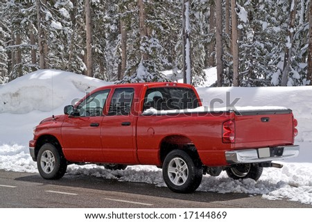 Shiny red truck measuring the depth of the snow
