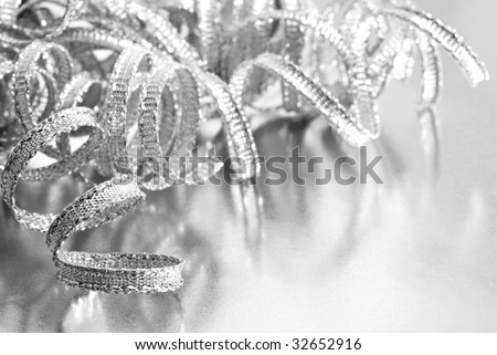 Shiny silver curling ribbon on reflective wrapping paper.  High key black and white macro with extremely shallow dof.  Copy space included.