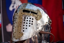 Shiny silver medieval iron knight helmet with a golden cross, full of scratches due to battles
