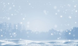shiny snowflakes on blurred winter landscape, christmas background with advertising space on snow cover, beautiful winter idyll