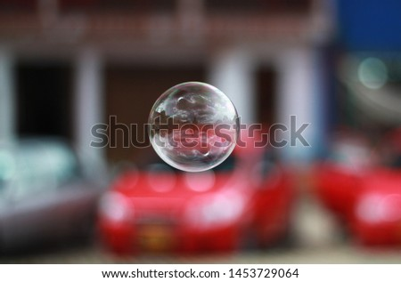 Shiny soap bubble with blurry background (shallow depth of field) reflections of the environment (outdoors)  #1453729064