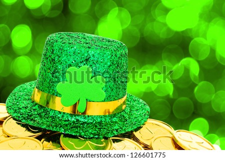 Shiny St Patrick's Day hat and gold coins on green twinkling background