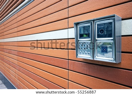 Shiny stainless steel intercom at a modern apartment block.