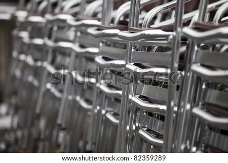 Shiny steel chairs stacked outside a restaurant