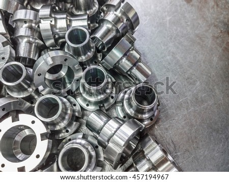 Shiny steel parts after cnc turning, drilling and machining on steel surface selective focus close-up composition background.
