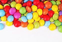Shiny sugar coated round chocolate balls as background. Candy bonbons multicolored texture. Round candies sweets pattern concept. Smarties. Food photo studio photography. Candy background