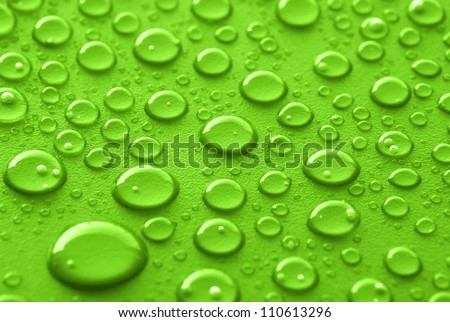 Shiny water drops sprayed on textured green surface.