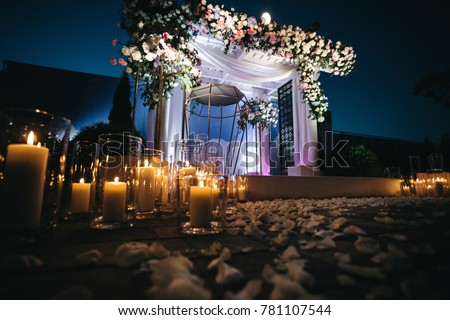 Shiny white candles stand on the ground in the darkness before wedding altar Сток-фото ©