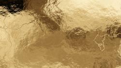 Shiny wrinkled golden foil texture. Crumpled metal background.
