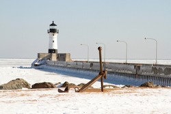 Ship anchor on shores of frozen Lake Superior next  to pier along shipping channel  with white lighthouse in Duluth, Minnesota, USA in winter.