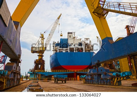 Ship and monumental crane in the shipyard.