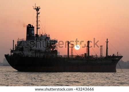 Ship at the harbor of Mumbai, India at sunset. - stock photo