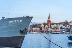 Ship at the quay in the port in front of the cityscape of Flensburg.